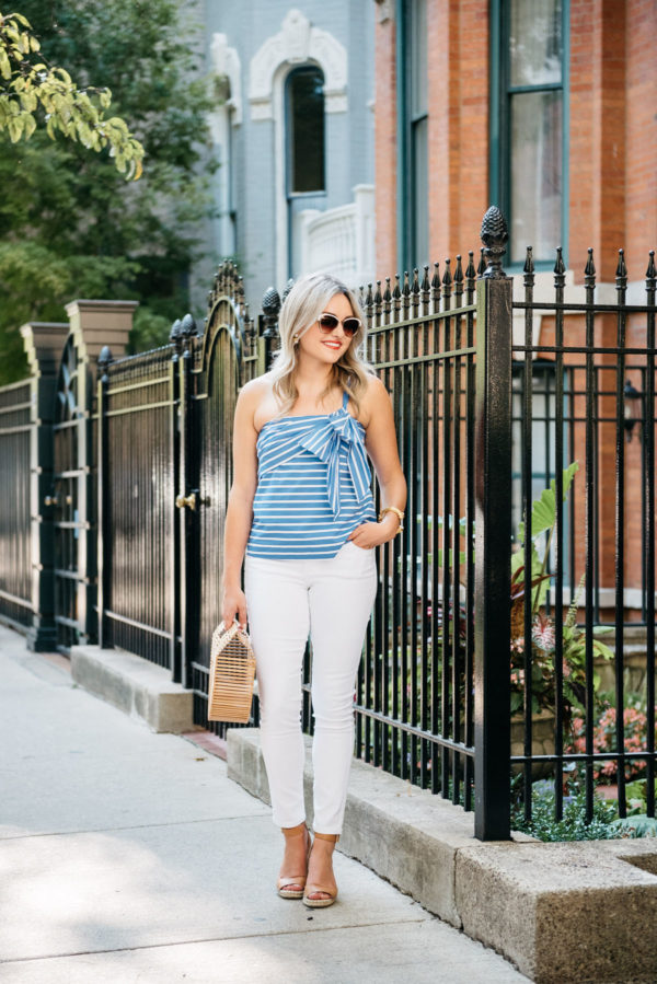 Chicago-based fashion-focused blogger Bows & Sequins wearing a blue and white striped bow tie J.Crew top with Old Navy Rockstar jeans, Vince Camuto wedges, and a Cult Gaia bamboo Arc bag.