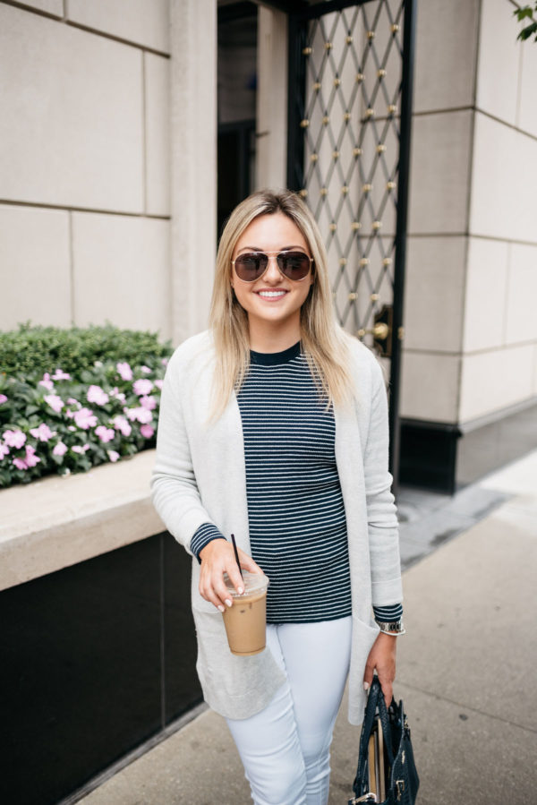 Bows & Sequins wearing a cream cardigan, an Old Navy navy striped sweater, white jeans, and Gucci aviators with a David Yurman bracelet.
