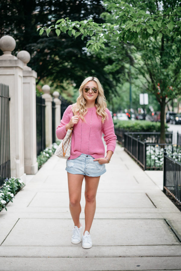 Bows & Sequins wearing a pink sweater with jean shorts and Stan Smith sneakers.