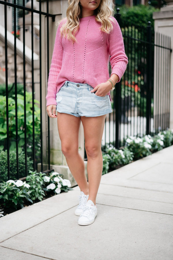 Bows & Sequins wearing a pink J.Crew sweater with jean shorts and Stan Smith sneakers.