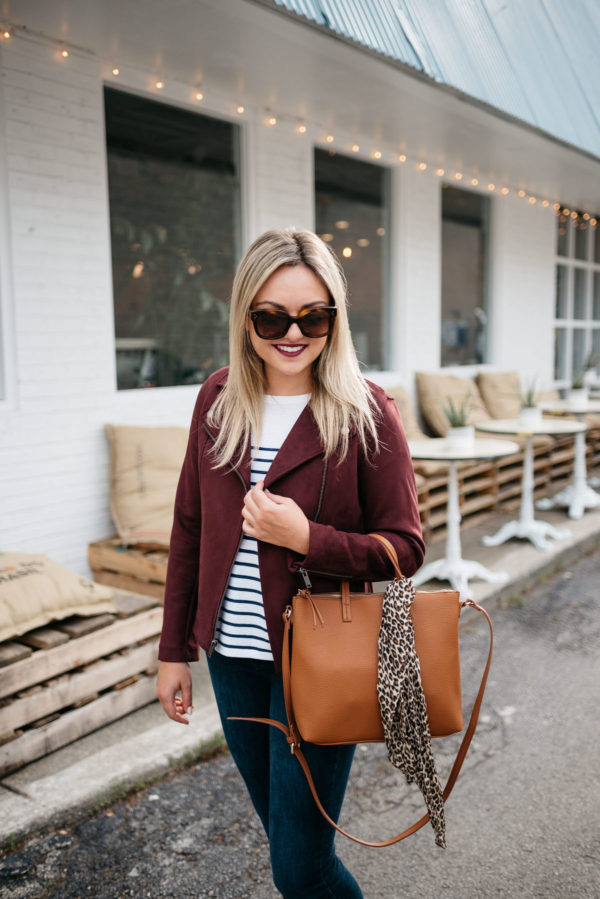 Fashion blogger Bows & Sequins sharing fall outfit inspiration: Celine sunglasses, a burgundy suede moto jacket, striped shirt, Bare Minerals matte liquid lipstick in Devious, and an Old Navy leather bag with a leopard scarf.
