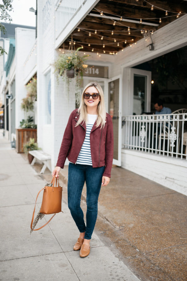 Bows & Sequins wearing a burgundy suede jacket, Old Navy Rockstar jeans, and a leather bag with Celine sunglasses.