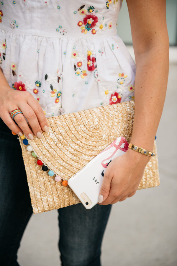 Style blogger Bows & Sequins wearing a J.Crew embroidered top and a BaubleBar cuff, holding a White Elephant Designs pom pom straw clutch and a Minnie & Emma flamingo phone case.