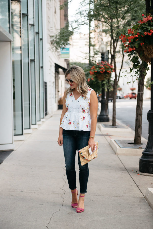Chicago lifestyle blogger Bows & Sequins wearing a colorful embroidered J.Crew peplum top with Paige jeans, a White Elephant Designs straw pom pom clutch, and Vince Camuto pink ankle strap heels.