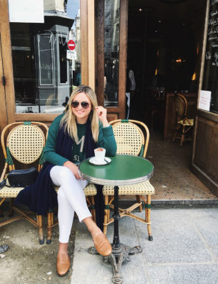 Jessica Sturdy wearing white jeans during the fall in Paris. Styled with leather loafers, a hunter green sweater, a navy cashmere scarf, and a Gucci handbag and sunglasses.