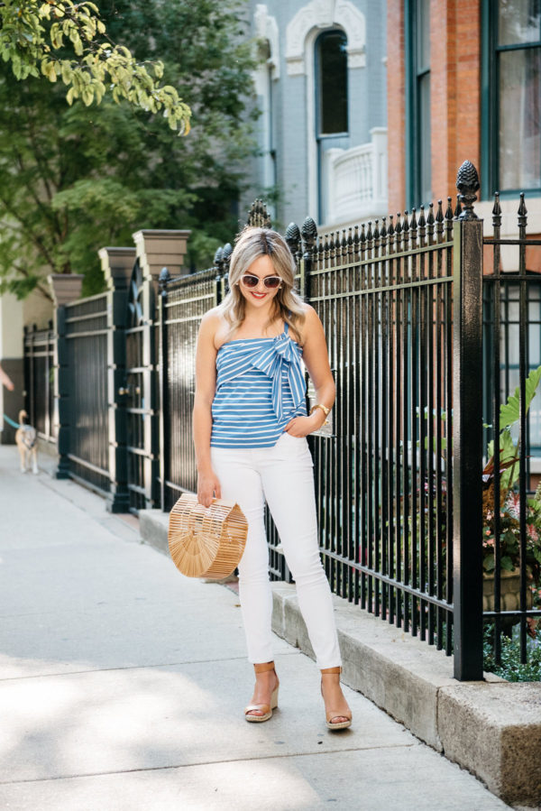 Chicago fashion and lifestyle blogger Bows & Sequins wearing a blue and white striped bow tie J.Crew top with Old Navy Rockstar white denim, Vince Camuto wedges, Call It Spring sunglasses, Julie Vos gold cuff, and a Cult Gaia bamboo Arc bag.
