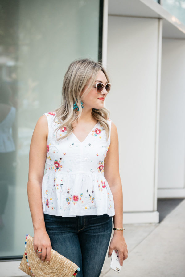Bows & Sequins wearing Call It Spring white sunglasses, BaubleBar Sardina earrings, and a J.Crew embroidered peplum top.