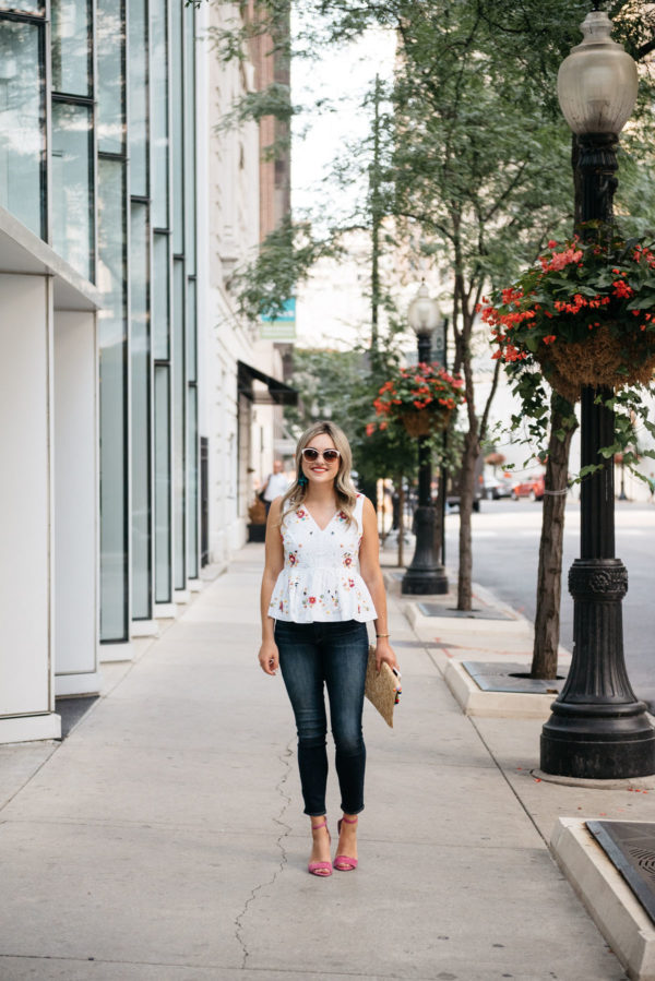 Fashion and lifestyle writer Bows & Sequins wearing Call It Spring white sunglasses, a J.Crew embroidered peplum top, Paige jeans, and Vince Camuto pink ankle strap heels.