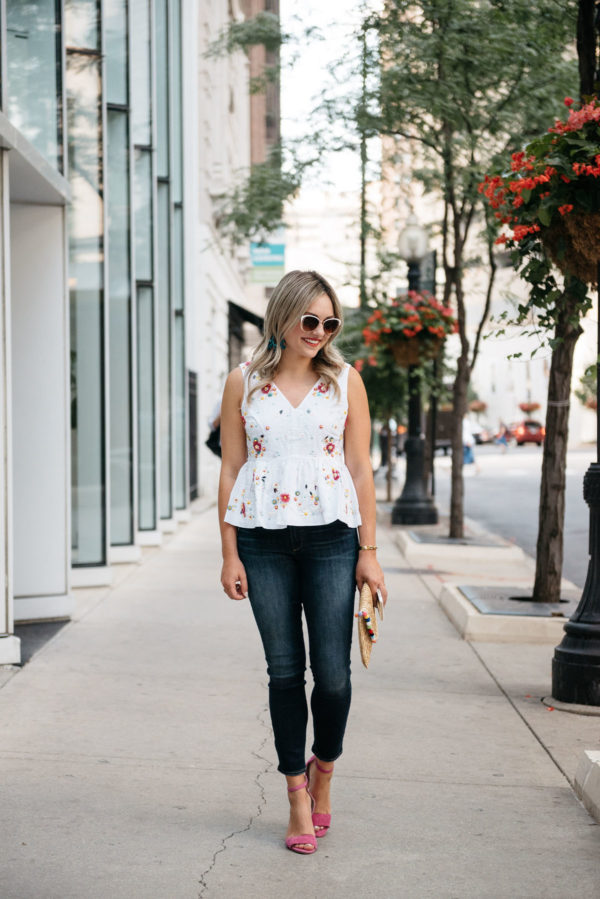 Chicago blogger Bows & Sequins wearing Call It Spring white sunglasses, a J.Crew peplum top, Paige jeans, Vince Camuto pink ankle strap heels, with a White Elephant Designs pom pom straw clutch.