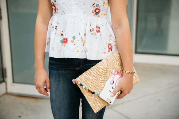 Bows & Sequins wearing a J.Crew embroidered peplum top and a BaubleBar cuff, holding a White Elephant Designs pom pom straw clutch and a Minnie & Emma flamingo phone case.