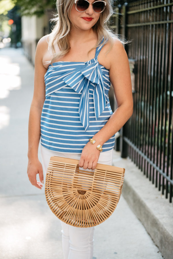 Chicago lifestyle blogger Bows & Sequins wearing Call It Spring sunglasses, a gold Julie Vos cuff, and a J.Crew bow tie striped top with a Cult Gaia bamboo Arc bag.