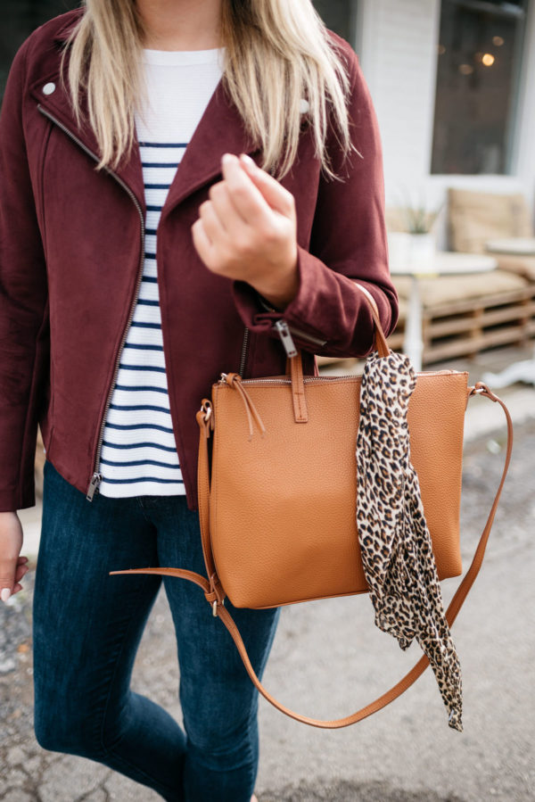 Fashion blogger Bows & Sequins sharing fall outfit inspiration: a burgundy suede moto jacket, striped shirt, and an Old Navy leather bag with a leopard scarf.