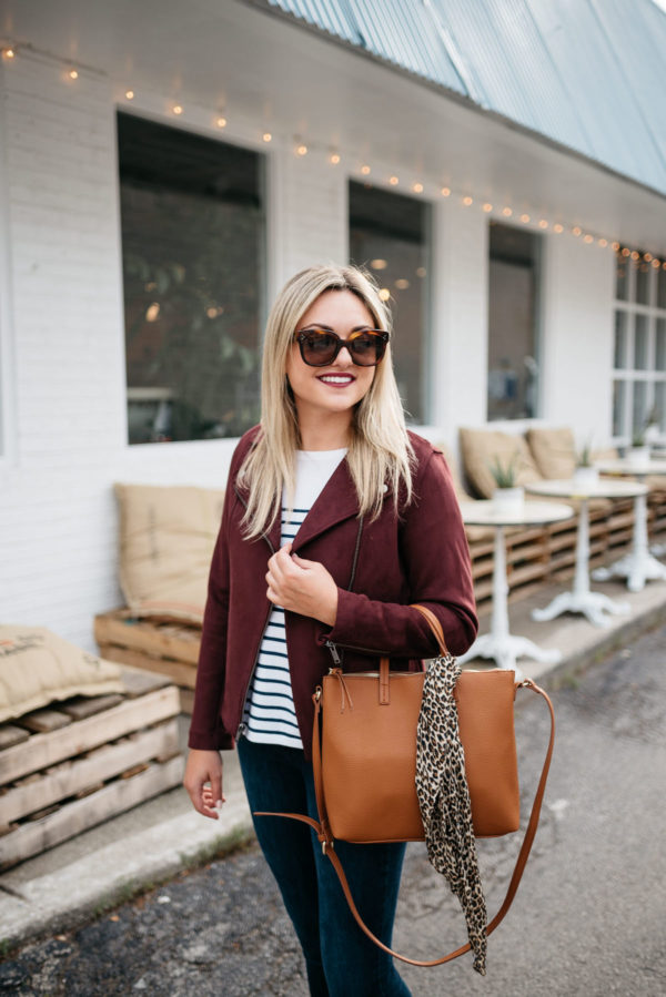 Jessica Sturdy of Bows & Sequins, a Chicago-based fashion-focused blog, wearing Celine sunglasses, a burgundy suede moto jacket, striped shirt, Old Navy Rockstar jeans, and a leather bag with a leopard printed scarf with Bare Minerals matte lipstick in Devious.