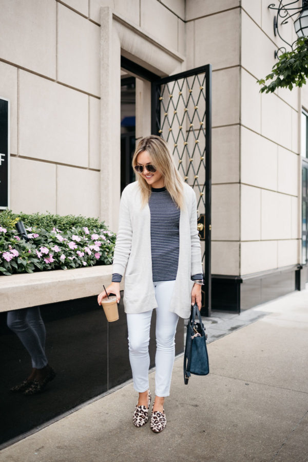 Chicago-based fashion-focused blogger Bows & Sequins wearing a cream cardigan, navy striped sweater, white jeans, and Kate Spade leopard loafers with Gucci aviators and a navy tote.