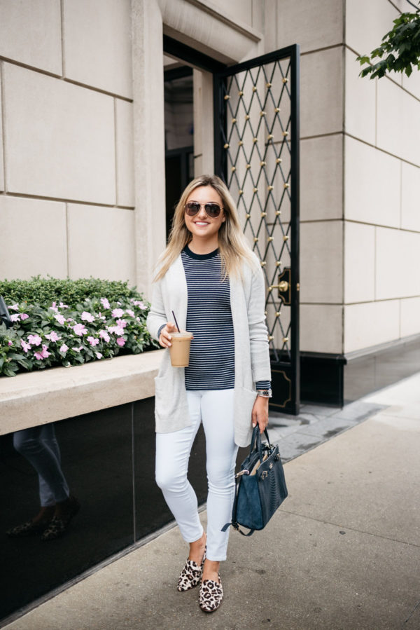 Bows & Sequins, a Chicago-based fashion-focused blogger, wearing an Old Navy cardigan, striped sweater, white jeans, and Kate Spade leopard loafers with a navy tote, David Yurman bracelet, Gucci aviators, and a Coach watch.