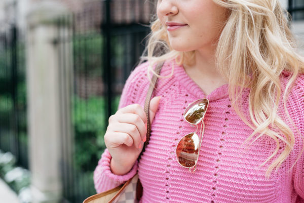 Bows & Sequins wearing a pink sweater with mirrored sunglasses.