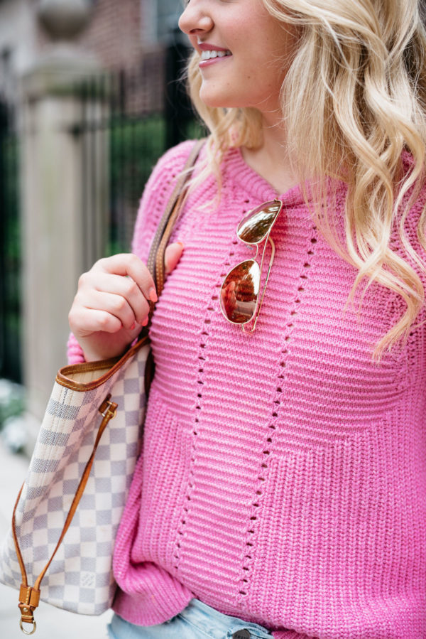 Bows & Sequins wearing a pink J.Crew sweater with her Louis Vuitton Neverfull bag.