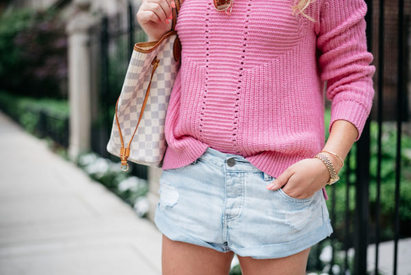 Bows & Sequins wearing a pink J.Crew sweater and jean shorts with her Louis Vuitton Neverfull bag.