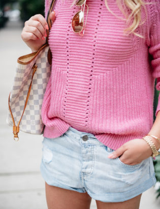Bows & Sequins wearing a pink J.Crew sweater and jean shorts with her Louis Vuitton Damier Azur Neverfull bag.