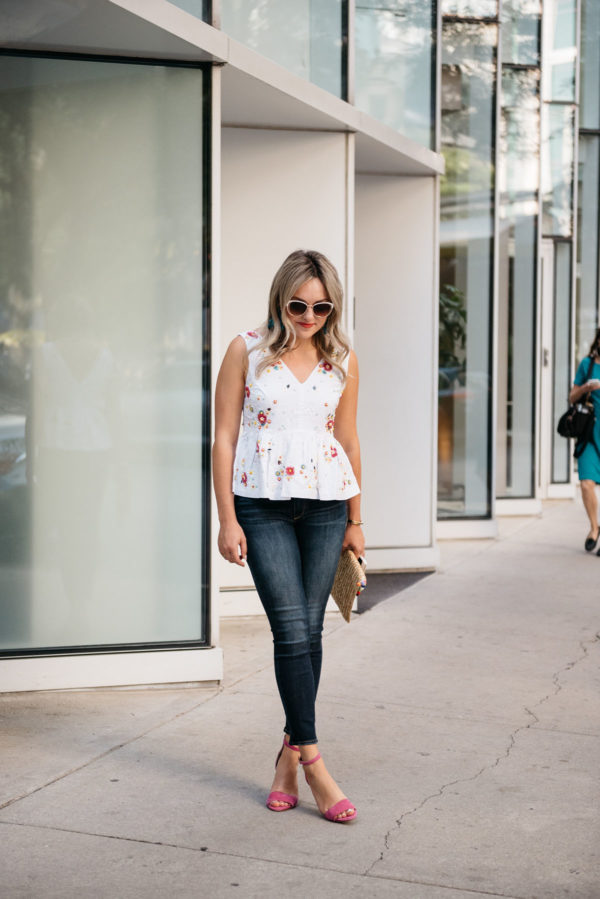 Style blogger Bows & Sequins wearing Call It Spring white sunglasses, a J.Crew peplum top, Paige jeans, Vince Camuto pink ankle strap heels, with a White Elephant Designs pom pom straw clutch.