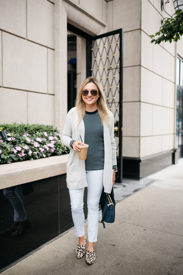 Lifestyle blogger Bows & Sequins wearing Gucci aviators, an Old Navy cardigan, striped sweater, white jeans, Kate Spade leopard loafers, and navy tote at the Waldorf Astoria in Chicago.