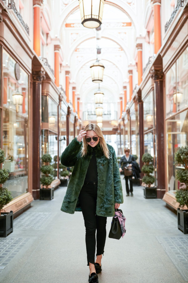 Bows & Sequins wearing a black turtleneck bodysuit, black jeans, bow mules, and a green fur coat in London.