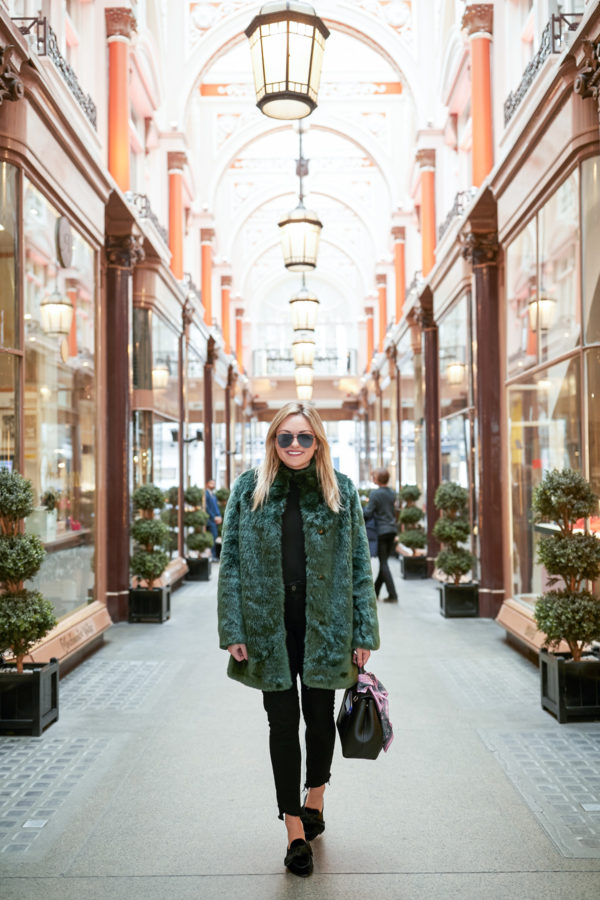 Bows & Sequins wearing a J.Crew black turtleneck, raw hem jeans, a Polene bag and a green faux fur coat.