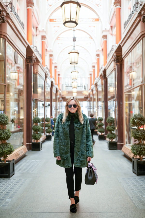 Bows & Sequins wearing black aviator sunglasses, a green faux fur coat, a black turtleneck from J.Crew, Paige skinny jeans, Sandro velvet bow mules, and a Polene top-handle bag.