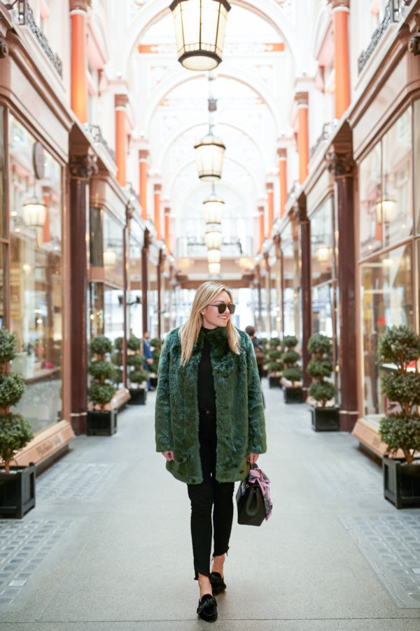 Bows & Sequins wearing a turtleneck bodysuit, black jeans, bow mules, black aviators, a Polene bag, and a faux fur green coat in London.