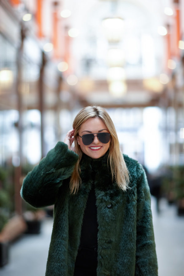 Bows & Sequins wearing matte black aviators and a green faux fur jacket in London.