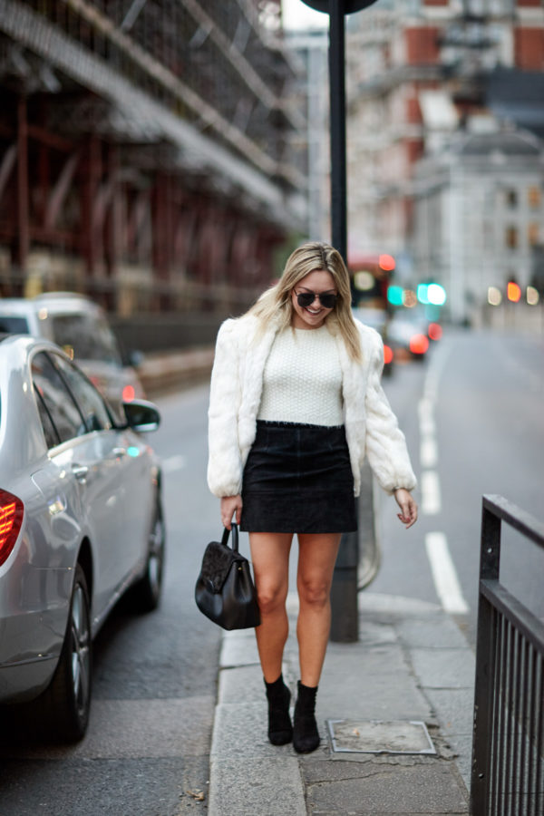 Travel blogger Bows & Sequins wearing a vintage white fur coat, H&M black suede skirt, and Steve Madden sock booties with a Polene leather satchel and Le Specs matte aviators in London.
