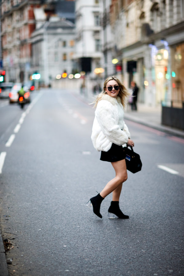 Travel and fashion writer Bows & Sequins wearing a vintage white fur coat, H&M black suede skirt, and Steve Madden sock booties with a Polene leather satchel and Le Specs matte aviators in London.