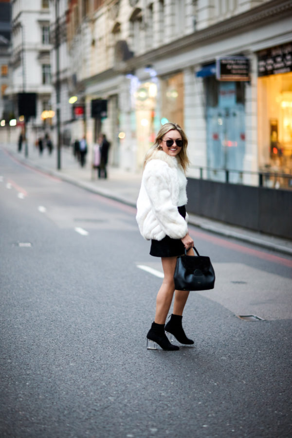 Travel blogger Bows & Sequins wearing a vintage white fur coat, H&M black suede skirt, and Steve Madden lucite heel sock booties with a Polene leather satchel and Le Specs matte aviators in London.