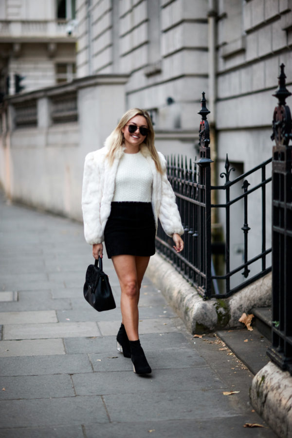 Travel blogger Bows & Sequins wearing a vintage white fur coat, black suede skirt, and sock booties with a leather satchel in London.