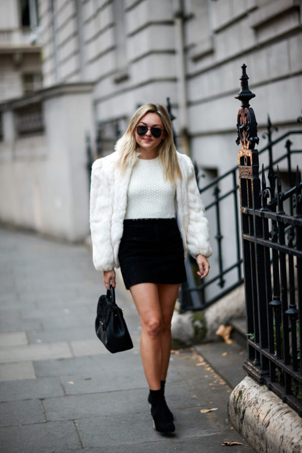 Fashion and travel blogger Bows & Sequins wearing a vintage white fur coat with a crop top, black suede skirt, and sock booties from Steve Madden with a Polene leather satchel.