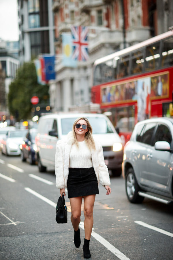 Travel writer Jessica Sturdy of Bows & Sequins wearing Le Specs black aviators, vintage white fur coat, and a black suede skirt with a Polene leather satchel in London.