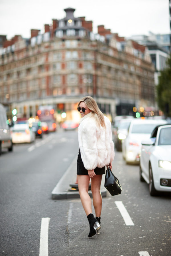 Bows & Sequins wearing Le Specs matte black aviators, a vintage fur coat, black suede H&M skirt, and lucite heel sock booties in London.