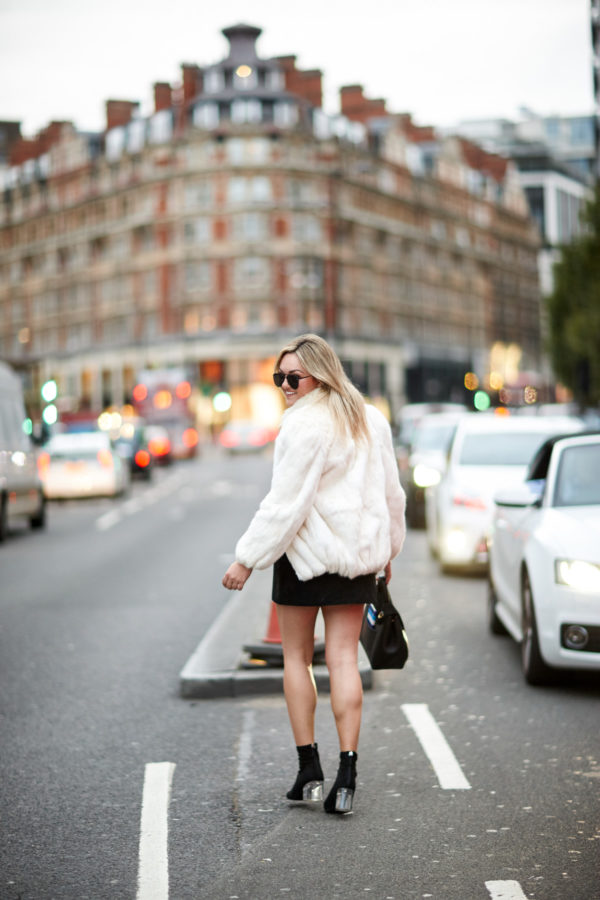 Bows & Sequins wearing a white fur coat, a black suede skirt, and lucite heel Steve Madden sock booties.