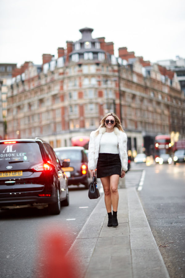 Bows & Sequins wearing a vintage white fur coat, crop top, and black suede skirt with lucite heel ankle sock booties and a leather satchel.