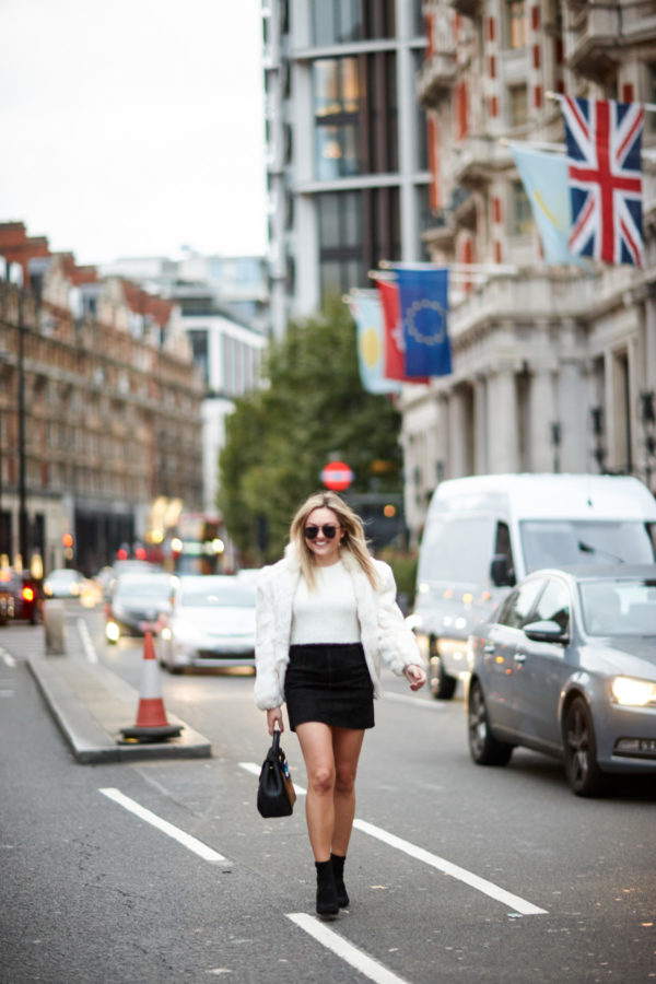 Bows & Sequins wearing a vintage fur coat, a white Lovers + Friends crop top, an H&M black suede skirt, Steve Madden lucite sock booties, and Le Specs matte black aviators in London.