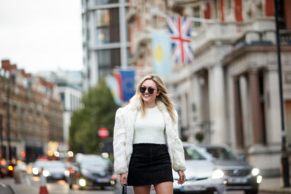 Travel and fashion blogger Bows & Sequins wearing a vintage white fur coat, a white crop top, and an H&M black suede skirt with matte black aviators.