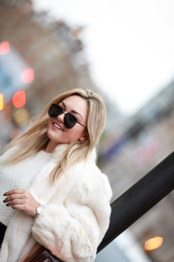 Travel writer Bows & Sequins wearing a white fur coat and Le Specs matte black aviators.