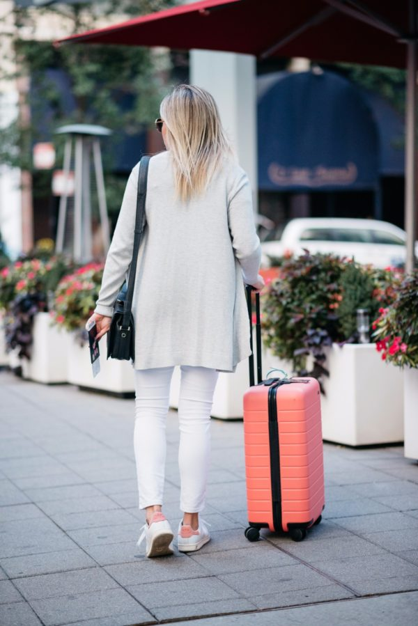 Bows & Sequins wearing an all white outfit with a pink Away x Gray Malin suitcase.