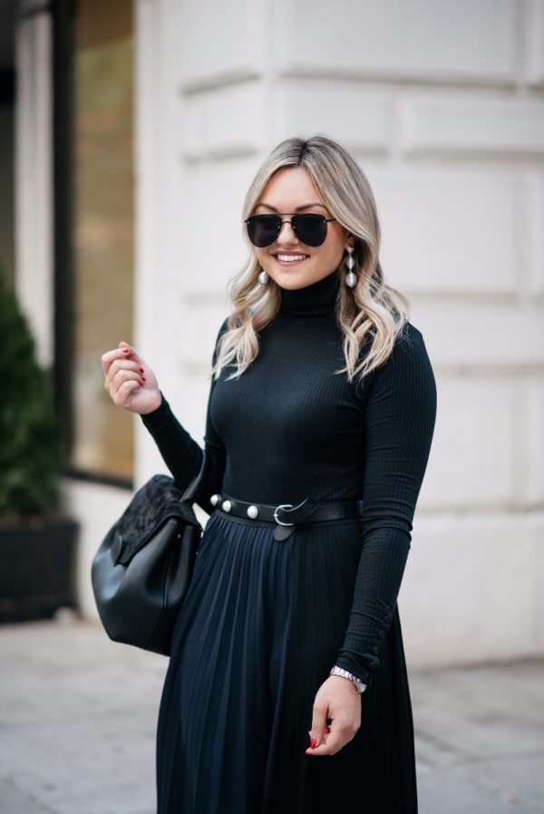 Chicago lifestyle blogger Bows & Sequins wearing a black turtleneck bodysuit and a navy and black pleated skirt with silver accessories, a pearl studded belt, and a Polene leather bag.