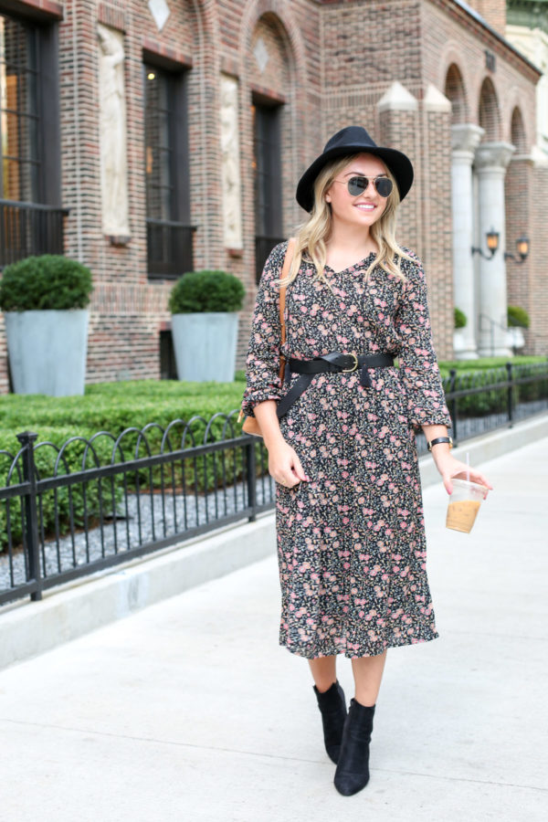 Jessica of the fashion-focused blog Bows & Sequins, wearing a black Old Navy hat, matte aviators, a black leather Madewell belt, and ankle booties with her Old Navy fall floral dress.