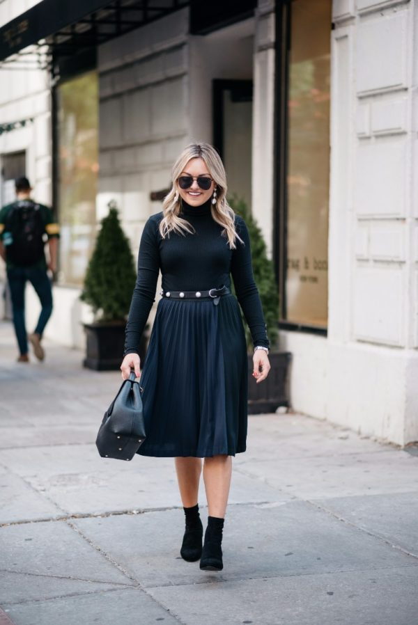 Bows & Sequins wearing a black turtleneck bodysuit, a Leith pleated skirt, and Steve Madden ankle boots.