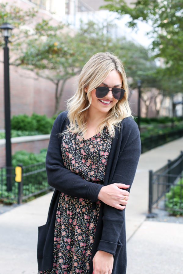 Bows & Sequins wearing matte aviator sunglasses, a black cardigan, and a floral midi dress from Old Navy for fall.