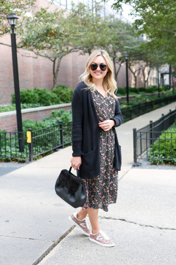 Chicago fashion blogger Bows & Sequins wearing a black cardigan, fall floral midi dress, and glitter sneaker with a black leather handbag.