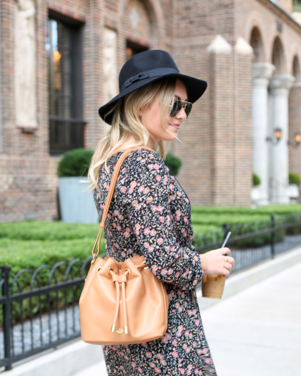 Fashion and lifestyle blogger Bows & Sequins wearing a black Old Navy hat, Ray-Ban aviators, and a floral dress with a Brahmin leather bag.