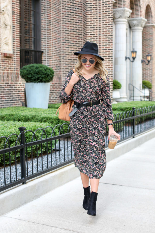 Bows & Sequins wearing a floral dress with a black leather belt, black ankle booties, Ray-Ban aviators, and a Brahmin leather bag.